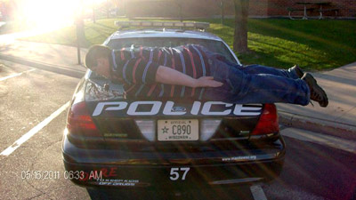 Teen planking on Cop car.